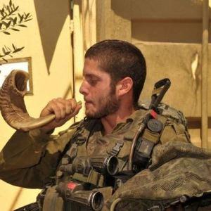 soldier blowing shofar at wall
